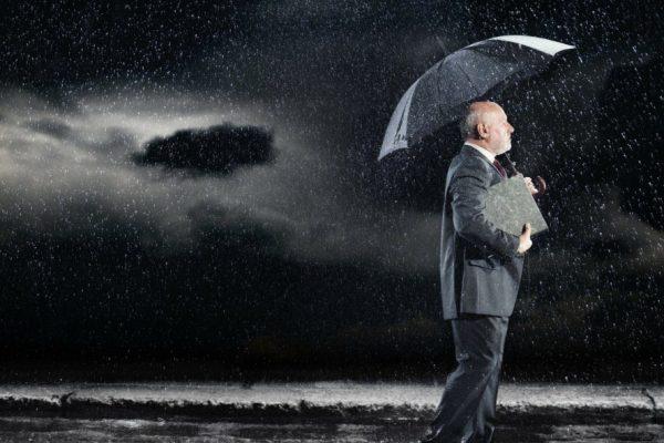 A man with an umbrella stands under a dark cloudy sky.