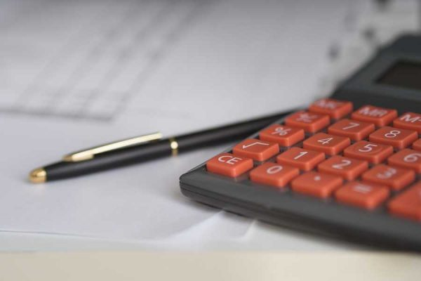 A calculator, pen, and paperwork sit on a desk.
