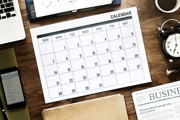 A calendar sits on a desk with other productivity tools.