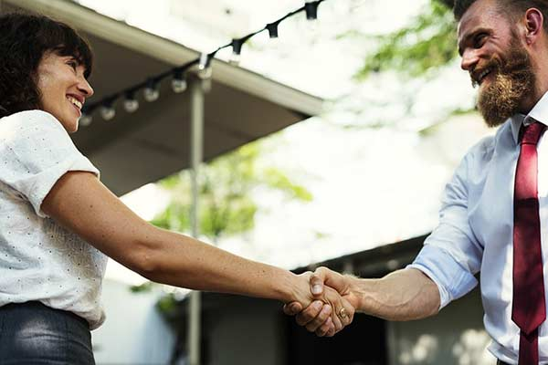 A homeowner and roofing contractor shake hands on a deal.