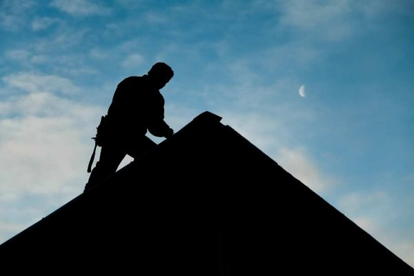 A roofer conducts a roof inspection silhouetted against an evening sky. roofing san marcos