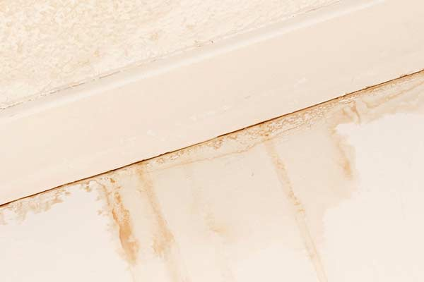 Water damage is visible on an interior ceiling and wall. roofing san marcos