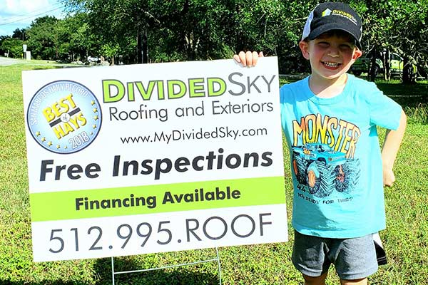 Divided Sky owner John Hardy's son Tucker stands beside a sign advertising the company.