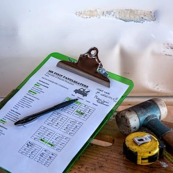 Insurance paperwork sits next to a wall with water damage caused by a leaking roof.