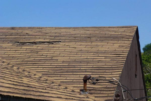 Roof with shingle damage awaiting repairs from our San Marcos roofing team.
