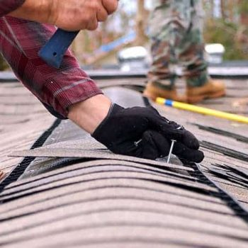 A roofer secures a row of shingles on a roof.