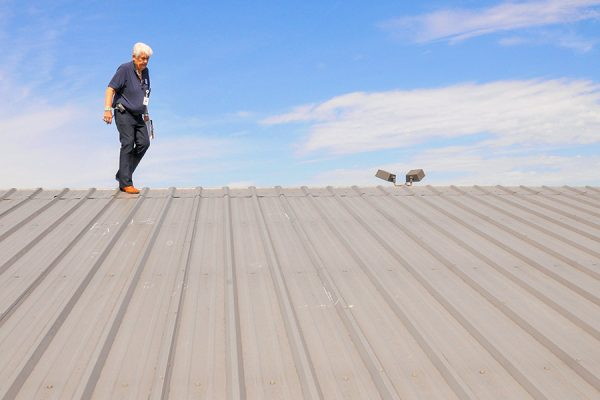 Man Inspection a Metal Roof