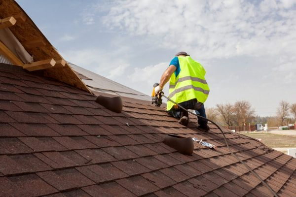 Roofer repairing shingles on roof