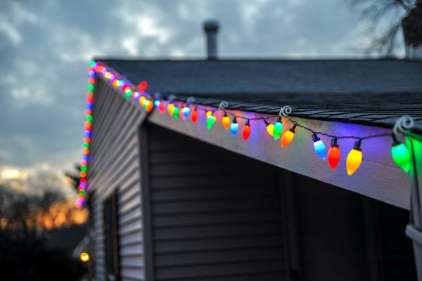 Christmas lights hung safely along a roof's edge with tips from our San Marcos roofing company contractors