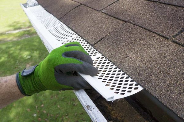 Professional installing commercial and residential gutters in San Marcos