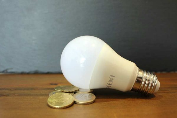 A lightbulb on a desk with some coins