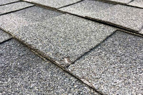 A roof shingle with difficult to spot damage
