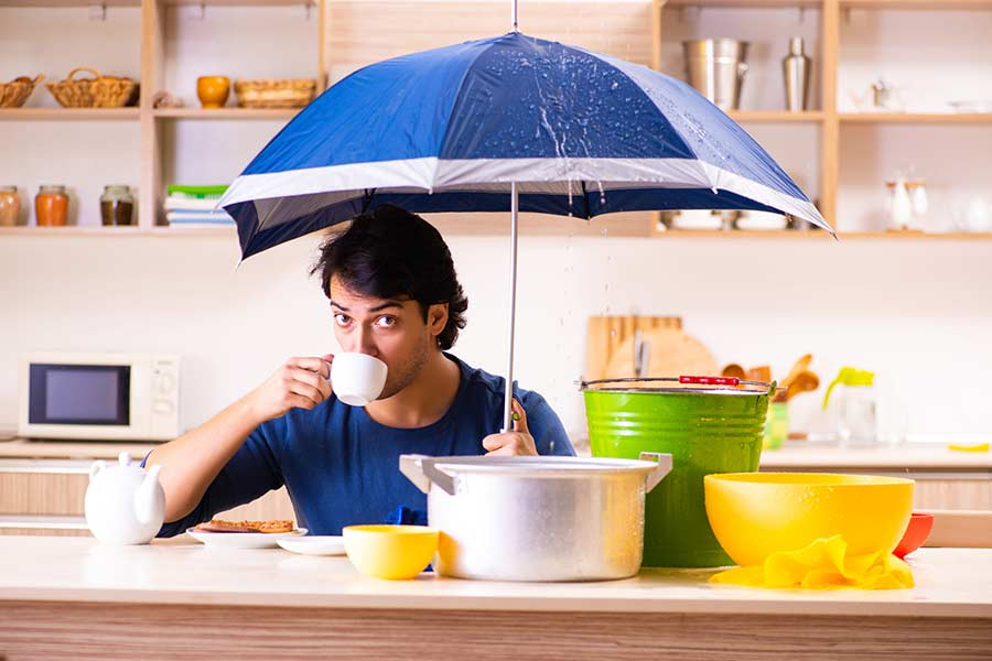 Man holding an umbrella to shield against a roof leak