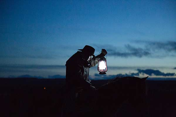 Dramatic shot of a cowboy with a lantern silhouetted against a night sky