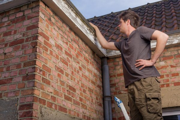 A man inspectin his home for his summer roof mainteance checklist.