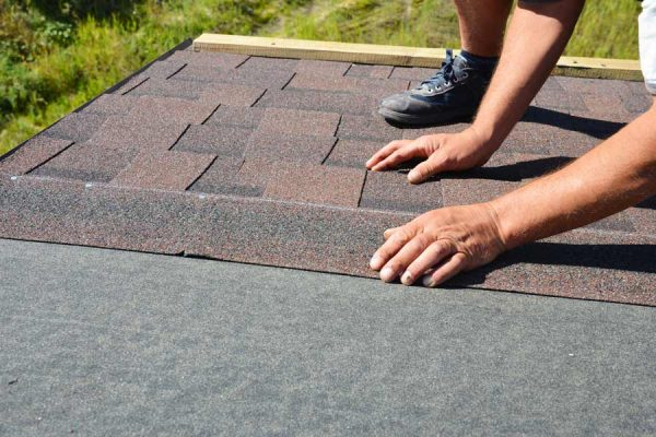 Roofer installing shingles on top of roof underlayment