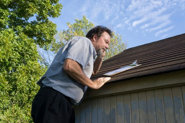 An insurance agent on their phone inspecting a roof for damage.