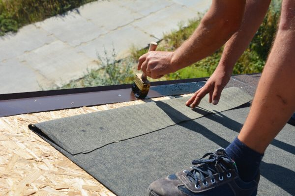 A roofer installing underlayment for a roof.